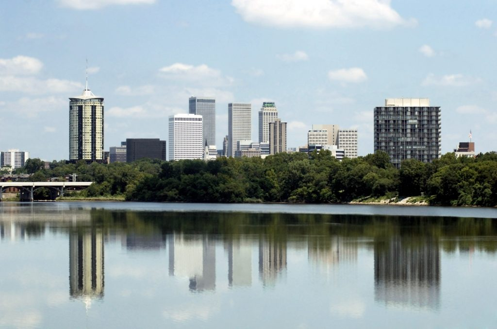 Skylin view of the city of Tulsa, Oklahoma with buildings reflected in the Arkansas River.
