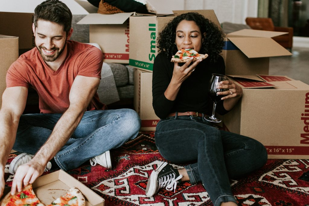 Two people eating pizza after moving into their new home.